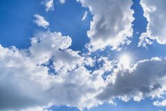 Bright blue cloudy sky with sun rays