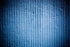 Bright blue color cement coarse facade wall with grooves as an empty rustic surface texture background with vignetting. Bright blue color cement coarse facade royalty free stock photography
