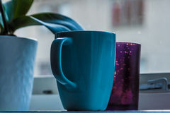 Bright blue cup standing on window board Royalty Free Stock Image