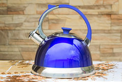 Bright blue kettle on the tablecloth table. Royalty Free Stock Image