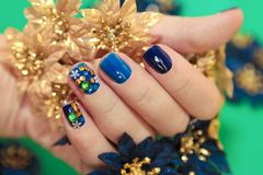 Bright blue manicure with the design of rhinestones stock photography