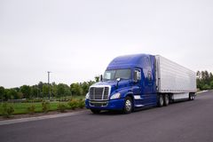 Bright blue big rig semi truck with reefer running on the road. Bright blue modern popular huge comfortable big rig semi truck for professional commercial Royalty Free Stock Image