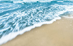 Blue ocean waves background with golden sand. Royalty Free Stock Photos