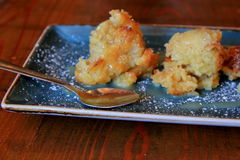 Bright blue plate with bread pudding, sprinkled with confectionary sugar Royalty Free Stock Image