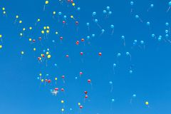 Bright blue, red and yellow air balloons rise up in the blue sky. Balls background