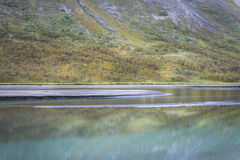 Bright blue river reflecting autumn colored mountain slope in rapadalen valley landscape Sweden Royalty Free Stock Image