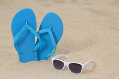 Bright blue rubber flip flops and sunglasses on the sand Stock Image