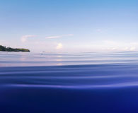 Bright blue sea with ripples and distant shore. Double landscape with sea water and sky. Royalty Free Stock Photos