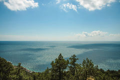 Bright blue sea and rocks and forest on a sunny day in the Crimea. Crimean summer lamdscape. Aya cape, coniferous forest and rocks Royalty Free Stock Images