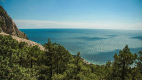 Bright blue sea and rocks and forest on a sunny day in the Crimea. Crimean summer lamdscape. Aya cape, coniferous forest and rocks Stock Photos