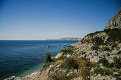 Bright blue sea and rocks and forest on a sunny day in the Crimea. Crimean summer lamdscape. Aya cape, coniferous forest and rocks Stock Photo