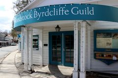 Bright blue sign welcoming visitors into the town, Woodstock Byrdcliffe Guild, Woodstock, New York, 2019. Old historic architecture seen throughout the village stock images