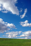 Bright Blue Sky with Clouds and Grass. Blue sky with clouds and green grass stock photo