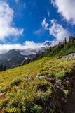bright blue sky with fluffy white clouds over a mountain landscape stock photo