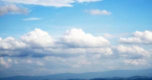 Bright blue sky with many drifting clouds Stock Image