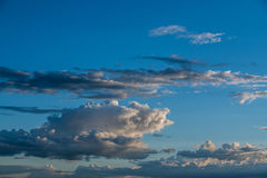 Bright blue sky , puffy white clouds, sunset. An imgae of blue sunset sky with puffy clouds Royalty Free Stock Photo