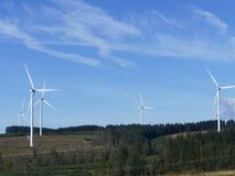 Landscape of Wind turbines power. Bright blue sky with  six large wind turbines set in a green forest South Wales Stock Photography