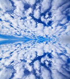 Bright blue sky white clouds mirrored on water Royalty Free Stock Photo