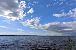 Bright blue sky with white clouds over the shore of the lake Stock Photo