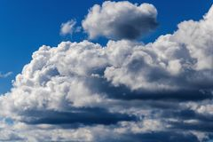 Bright Blue Sky with White Cumulonimbus Clouds. Cumulonimbus clouds are dense, vertical, towering clouds commonly associated with instability in the atmosphere Royalty Free Stock Image