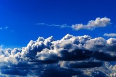 Bright Blue Sky with White Cumulonimbus Clouds. Cumulonimbus clouds are dense, vertical, towering clouds commonly associated with instability in the atmosphere Stock Photos