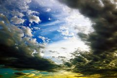 A bright blue sky with white and dark clouds at sunse by oil painting filter stock photography