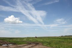 Bright blue summer sky the field and tractor. The Russian heartland provinces remote place dirt road unpaved road earth road dirt track soil Royalty Free Stock Image