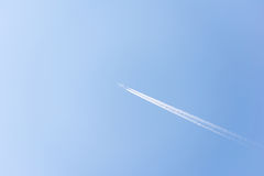 Airplane flying high in the sky with vapor trails. Bright blue summer sky with a single commercial airplane flying. Contrails follow the plane as it speeds Royalty Free Stock Photo