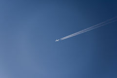 Airplane flying high in the sky with vapor trails. Bright blue summer sky with a single commercial airplane flying. Contrails follow the plane as it speeds Stock Photo