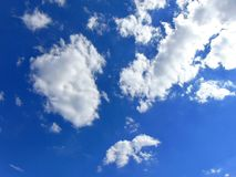 Bright Blue Summer Sky. With white, fluffy clouds royalty free stock photography