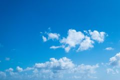 Blue sky background with fluffy white clouds. A bright blue sunny sky background with fluffy wispy white clouds Stock Image
