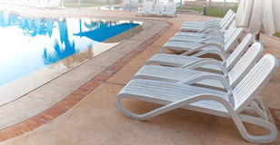 Bright blue swimming pool and empty resting chairs Stock Image