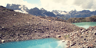 Bright blue water in the alpine lake - retro filter photo. Stock Images