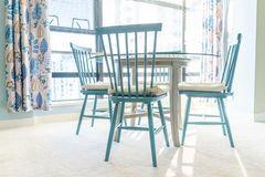 Bright, blue and white colorful dining table and chairs, with blue and white decor and a designed home interior scheme. Sunbeams royalty free stock photos