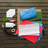 Craft Materials on Slatted Wood Table. Bright blue, white, green, and red paper with glue scissors tape and feathers ready for craft art Stock Photo