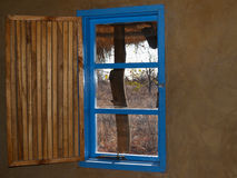 Bright blue window with open slat slat wooeden shutter and view Stock Photography