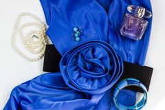 Bright blue women`s dress and accessories on a white background. Flower belt, pearl necklace, earrings, bracelet and perfume. stock photos