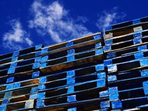 Bright blue wooden shipping palettes. Stacked wooden shipping palettes painted bright blue in strong sunlight beneath a deep and cloudy blue sky Royalty Free Stock Image
