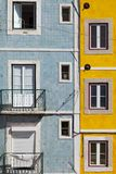 Colorful building with windows. Bright blue and yellow facade with square symmetrical windows in Lisbon, Portugal royalty free stock photo