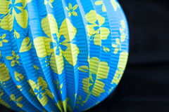 Bright Blue Yellow Flowered Chinese Paper Lantern. Pretty chinese paper lantern isolated on black background. Bright blue paper lantern with vibrant yellow Stock Images