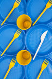 Bright blue and yellow plastic disposable tableware, background Royalty Free Stock Image