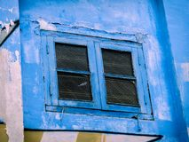 Colourful Blue Window with Shutters on A Street Art Wall. Bright, bold blue old rustic weathered wooden window shutters on a grafitti wall of angular colourful Royalty Free Stock Photos