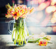 Bright bouquet of tulips in glass jug on table at sunny spring day background with bokeh Royalty Free Stock Image