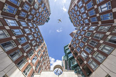 Bright brick house at the Clio place. Parallel up view of a bright brick houses with a plane at the Clio place, the center of The Hague city, Netherlands Royalty Free Stock Photo