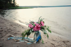 Bright bridal bouquet with roses and ribbons on the beach Royalty Free Stock Image