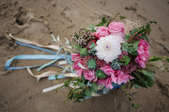 Bright bridal bouquet with roses and ribbons on the beach Royalty Free Stock Photo