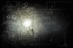 Bright bulb Illuminates icons on chalkboard. Bulb Illuminates mathematics and business icons on the school chalk board. 3d illustration Royalty Free Stock Photography