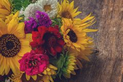 Bright fall bouquet. Bright bunch of fresh fall flowers on wooden table, retro toned royalty free stock photo