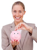 Bright businesswoman putting coins in a piggy bank Royalty Free Stock Photo