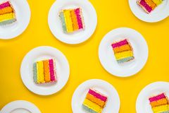 Bright cake pattern. Top view set of rainbow cake slices on white round plates on yellow background. Happy bithday, party layout royalty free stock images